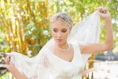 Ruhige blonde Braut, die heraus ihren Schleier hält Lizenzfreie Stockfotos