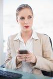 Ruhige blonde Geschäftsfrauversenden von sms-nachrichten Stockbild
