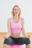 Ruhige blonde schwangere Frau, die auf Übungsball sitzt Lizenzfreie Stockfotos