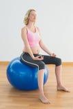 Ruhige blonde schwangere Frau, die auf Übungsball sitzt Stockfotos