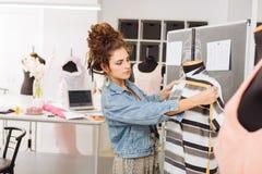 Ruhige Damenschneiderin, die Maßband beim Arbeiten mit Kleidung verwendet stockbilder