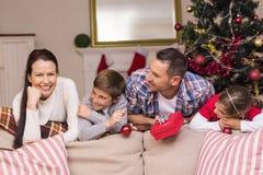 Ruhige Familie, die auf der Couch sich lehnt Lizenzfreie Stockbilder