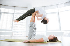 Ruhige Frau übendes acro Yoga mit Partner Lizenzfreie Stockfotos