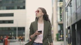 Ruhige Frau in der roten Sonnenbrille gehend in die Straße, die Smartphoneschirm betrachtet stock video footage