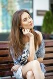 Ruhige Frau des Brunette, die auf der Bank in der Sommerstraße sitzt Stockfoto