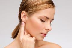 Ruhige Frau, die ihr Ohr berührt lizenzfreie stockfotografie