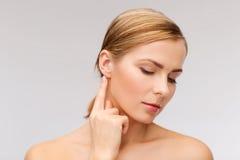 Ruhige Frau, die ihr Ohr berührt lizenzfreie stockbilder