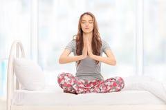 Ruhige Frau, die mit ihren Augen geschlossen meditiert Stockbild