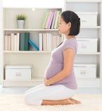 Ruhige Frau, die zu Hause meditiert Lizenzfreies Stockfoto