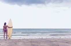 Ruhige Frau im Bikini mit Surfbrett auf Strand Stockfoto