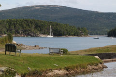 Ruhige Gebirgsszene mit See, Boote, Bank, Gras Lizenzfreies Stockfoto