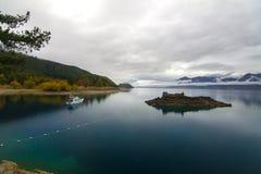 Ruhige Herbstlandschaft, reiner tiefer blauer See mit Wasserreflexion und Feiertagsboot, Otago-Hügel, Land New Zealand See Hawea lizenzfreies stockbild