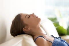 Ruhige junge Frau, die auf gemütlichem Sofa, atmende Frischluft sich entspannt stockbild