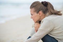 Ruhige junge Frau, die auf kaltem Strand sitzt Lizenzfreies Stockbild