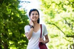 Ruhige junge Frau, die in den Park geht Stockfotografie