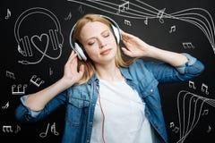 Ruhige junge Frau, die ihre Augen beim Hören Musik in den Kopfhörern schließt Stockfotografie