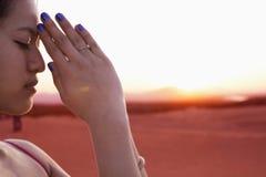 Ruhige junge Frau mit Augen schloss und Hände zusammen in der Gebetshaltung in der Wüste in China, Seitenansicht Stockfotos