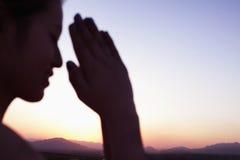 Ruhige junge Frau mit Augen schloss und Hände zusammen in der Gebetshaltung in der Wüste in China, Fokus auf Hintergrund Lizenzfreies Stockbild