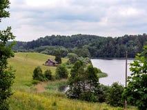 Ruhige Landschaftslandschaft mit grünen Feldern, kleinem Holzhaus und See am Sommertag lizenzfreie stockfotografie