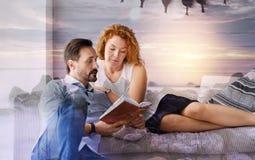 Ruhige liebevolle Paare, die beim Ablesen eines interessanten Buches aufmerksam schauen lizenzfreies stockbild