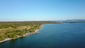 Ruhige Luftlandschaft des Meerwasserraumes, Küstenlinie wird von den grünen Bäumen am sonnigen Tag umfasst stock video
