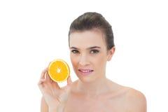 Ruhige natürliche braune behaarte vorbildliche haltene Hälfte einer Orange Lizenzfreie Stockbilder
