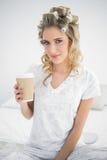 Ruhige recht blonde tragende Haarlockenwickler, die Kaffee halten lizenzfreies stockfoto