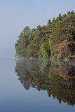 Ruhige Reflexionen auf schottischem Loch mit Landschaft Stockfoto