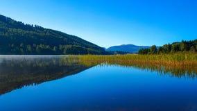 Ruhige Reflexionen auf Wasser mit Landschaft Stockfotos