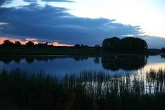 Ruhige Teichoberfläche mit Holz im netten Sonnenaufgang mit Dämmerung und Nebel Lizenzfreie Stockfotos