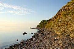 Ruhige und helle Küstenlinie mit der Klippe steil Stockfotografie
