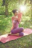 Ruhige und ruhige Frau, die aufmerksames Bewusstsein durch das Meditieren in der Natur mit Sonnenaufflackern übt Stockfotos