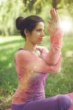 Ruhige und ruhige Frau, die aufmerksames Bewusstsein durch das Meditieren in der Natur mit Sonnenaufflackern übt Lizenzfreie Stockbilder