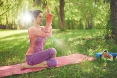 Ruhige und ruhige Frau, die aufmerksames Bewusstsein durch das Meditieren in der Natur mit Sonnenaufflackern übt Lizenzfreies Stockbild