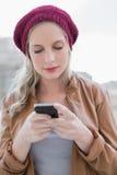 Ruhige zufällige blonde Versenden von SMS-Nachrichten draußen Stockfotos