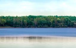 Ruhiger blauer See mit etwas gekräuselter Oberfläche vor einem Wald mit dichtem Baumbestand vor einem bewölkten Himmel lizenzfreie stockbilder
