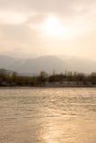 Ruhiger Fluss bei Sonnenuntergang mit goldenem Licht Stockfoto