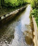 Ruhiger Fluss in einem Abzugsgraben oder in einer Gosse unter einer Brücke von Rohren in einer Kleinstadt Stockbild