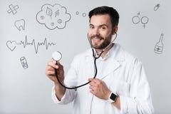 Ruhiger freundlicher Doktor, der ein Stethoskop beim Arbeiten hält Stockfotografie