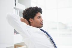 Ruhiger Geschäftsmann, der bei der Arbeit sich entspannt Stockfotos