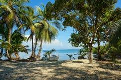Ruhiger karibischer Strand mit Schattenbäumen und Boot Lizenzfreies Stockbild