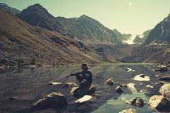 Ruhiger Mann, der im Urlaub auf einem Felsen betrachtet den See und die Berge am Sommerabend sitzt See kucherlinskoe altai Touris lizenzfreies stockfoto