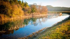 Ruhiger Nebenfluss, der die Grünebenen durchfließt Lizenzfreies Stockbild