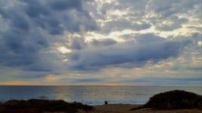 Ruhiger Ozean unter den flufy, bewölkten Himmeln Lizenzfreies Stockbild