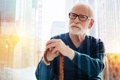 Ruhiger Pensionär, der den Abstand beim Lehnen auf dem Spazierstock untersucht lizenzfreie stockfotografie