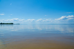 Ruhiger See, Himmel mit Wolken und Horizont Stockbild