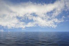 Ruhiger See mit den Kräuselungen, die zu einen blauen Himmel mit Wolken führen Lizenzfreies Stockfoto
