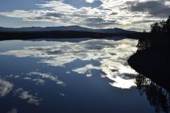 Ruhiger See mit Reflexionen vom Himmel Stockbilder