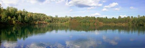 Ruhiger See umgeben durch Baumpanorama stockbild