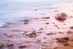 Ruhiger See und Steine auf Sonnenaufgang Stockfotos